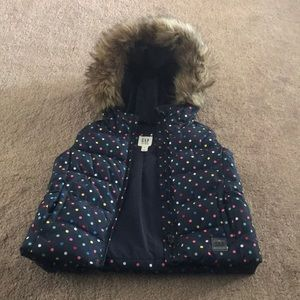 Adorable puffer vest with faux fur hood.